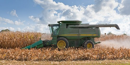 Green Farm Equipment and Machinery in a field. Loans offered by West Iowa Bank