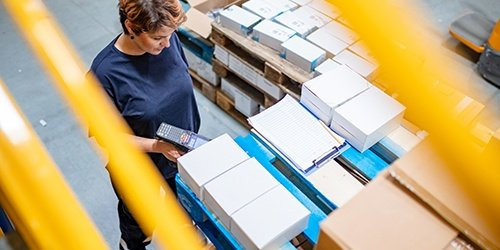Woman scanning boxes in factory. Operating Lines of Credit available at West Iowa Bank